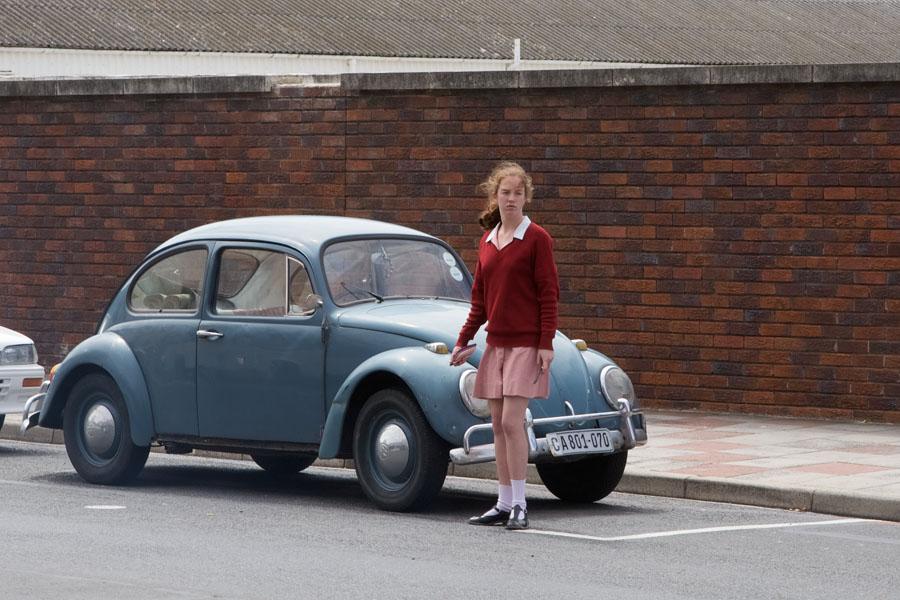 Mädchen in Schuluniform wartet neben uraltem VW-Käfer darauf, die Straße überqueren zu können