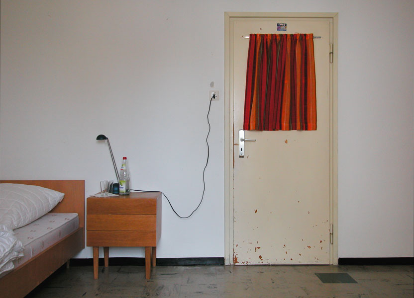 Simple room with scratched door with colorful window curtain next to a wooden bedside table