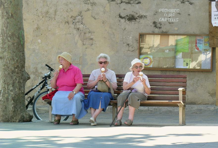Drei ältere Frauen sitzen auf einer Bank und essen Eis