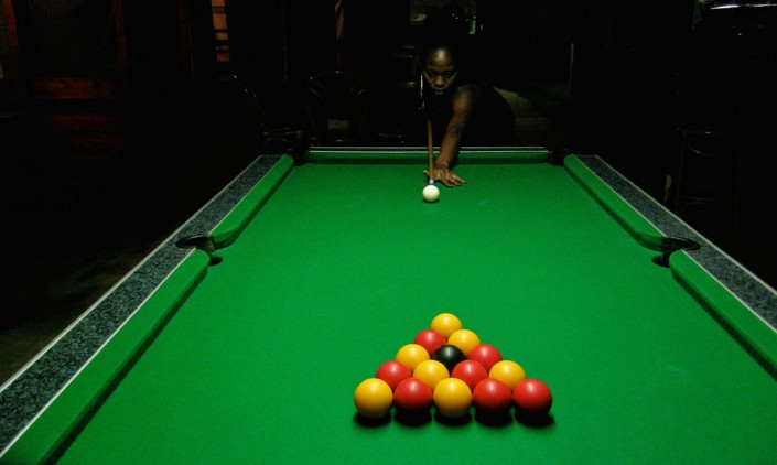 A dark-skinned woman seconds before the impetus of a new game of snooker