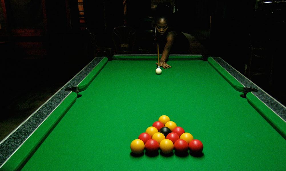 Eine dunkelhäutige Frau Sekunden vor dem Anstoß eines neuen Spiels Pool Billard