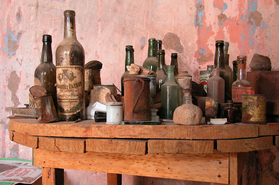 Still life of old glasses and bottles on an old wooden table