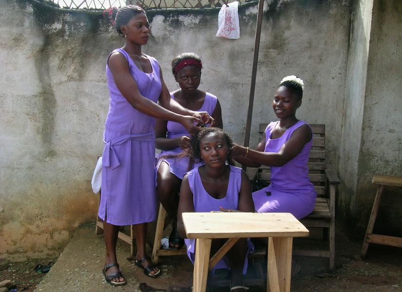 Drei junge dunkelhäutige Frauen aus Ghana in lila Kleidern flechten einer vierten Zöpfe