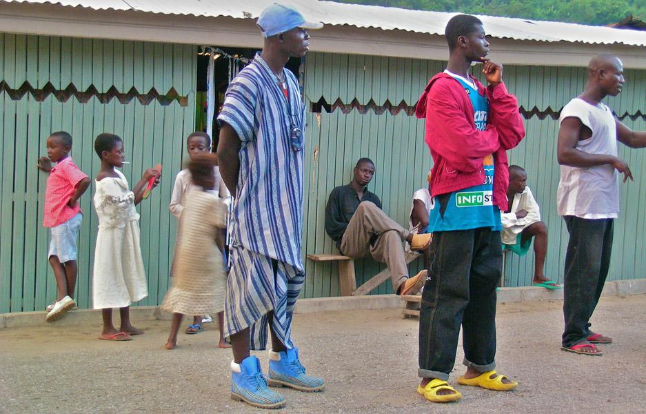 Männer aus Ghana in traditioneller und moderner Kleidung tragen Schuhwerk in blau und gelb