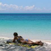 A young woman in blue bikini lying on her stomach on the beach of Pemba / Tanzania is reading