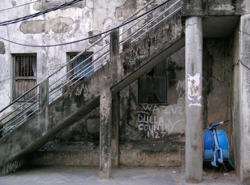 Das Wrack eines blauen Motorrollers steht unter der Außentreppe eines alten Gebäudes in Sansibar City