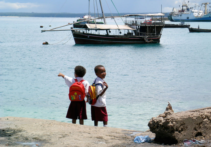 Two school kids with uniform and backpacks are standing in the harbor of Zanzibar City and point to the ships