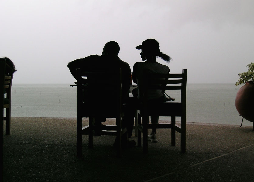 The black Silhuette of a couple against the gray sky on Lake Bosomtwe in Ghana