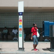 Dark-skinned woman with a cigarillo in jeans and red top standing on the street on a public phone