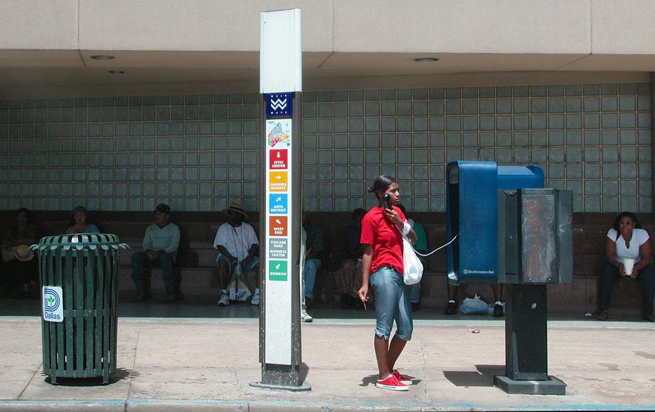 Dunkelhäutige Frau mit Zigarillo in Jeans und rotem Top steht auf der Straße an einem öffentlichen Telefon