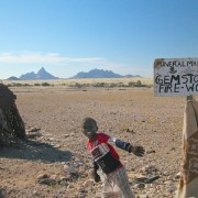 """A child in Namibia sells gem stones and firewood on the street under a sign labeled """"Mineral Marketing"""". In the background one can see the """"Spitzkoppe"""" mountains"""