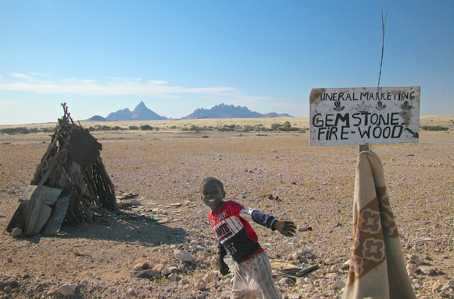 "A child in Namibia sells gem stones and firewood on the street under a sign labeled ""Mineral Marketing"". In the background one can see the ""Spitzkoppe"" mountains"