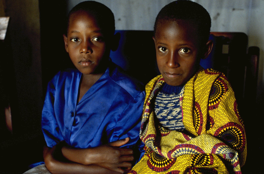 Two dark-skinned young brothers in blue and yellow clothes sit side by side