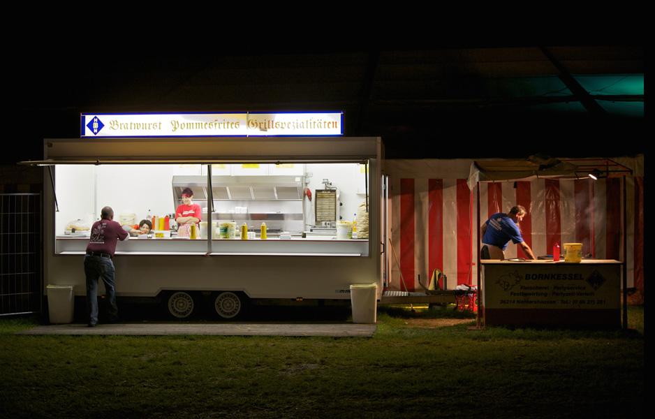 Mobile Bratwurst und Pommes Bude steht hell erleuchtet am Rand eines Dorffestes in Solz (Bebra)