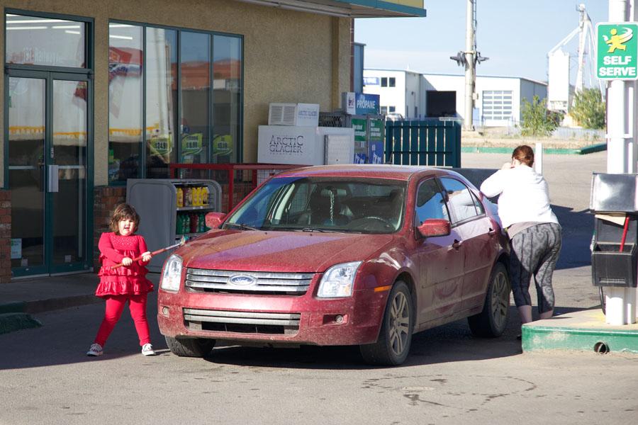 Mutter mit kleiner Tochter an einer Tankstelle. Die Mutter füllt den Tank, das Kind in rotem Kleid wischt die Scheinwerfergläser