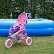 Teletubbie Tinky Winky in a pink play stroller in front of an inflatable children's paddling pool in the garden