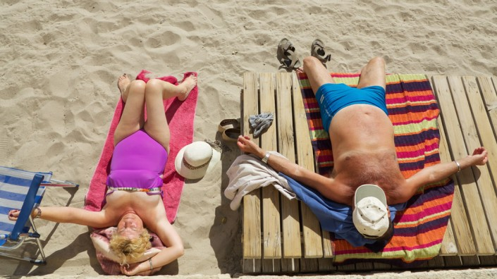 Sunbathe of an elderly couple in colorful swimwear at the beach in Torremolinos