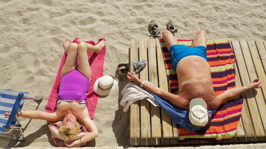 Sunbathe of an elderly couple in colorful swimwear at the beach in Torremolinos