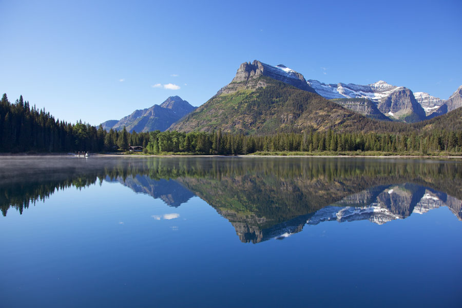 Blick über den spiegelglatten Upper Waterton Lake Richtung Goat Haunt Ranger Station Montana / U.S.A.
