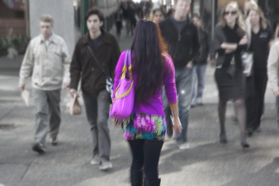 Rückansicht einer jungen Frau in geblümtem Rock und lilanem Pullover beim Überqueren einer belebten Straße