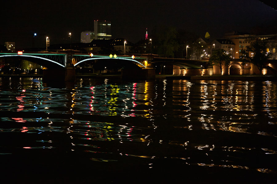 Light-reflecting waves on the River Main in Frankfurt with an illuminated Main Bridge in the background