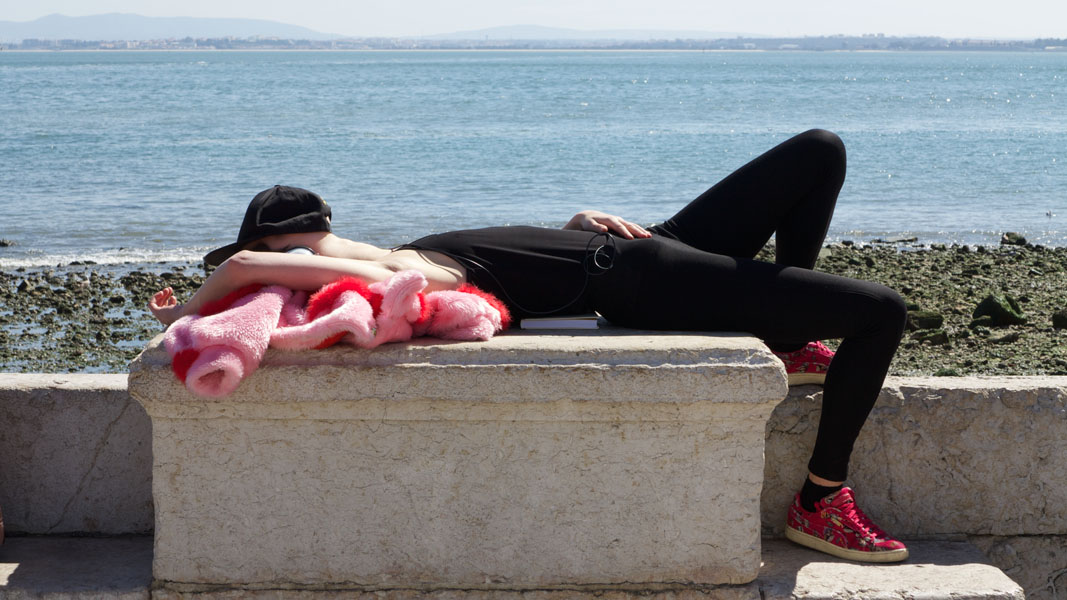 Black dressed young woman with hat over her face lying on a rock on the banks of the river Tajo taking a nap