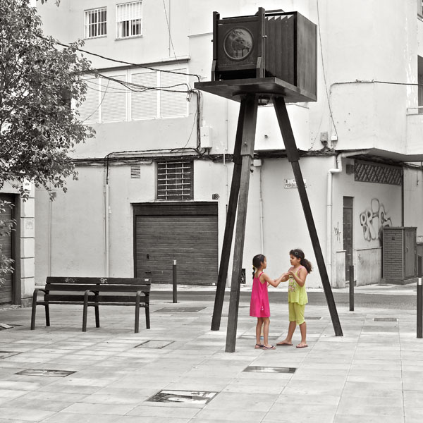 Zwei Kinder spielen unter der Kameraskulptur auf dem Plaza Manuel Falces López in Almeria / Andalusien / Spanien