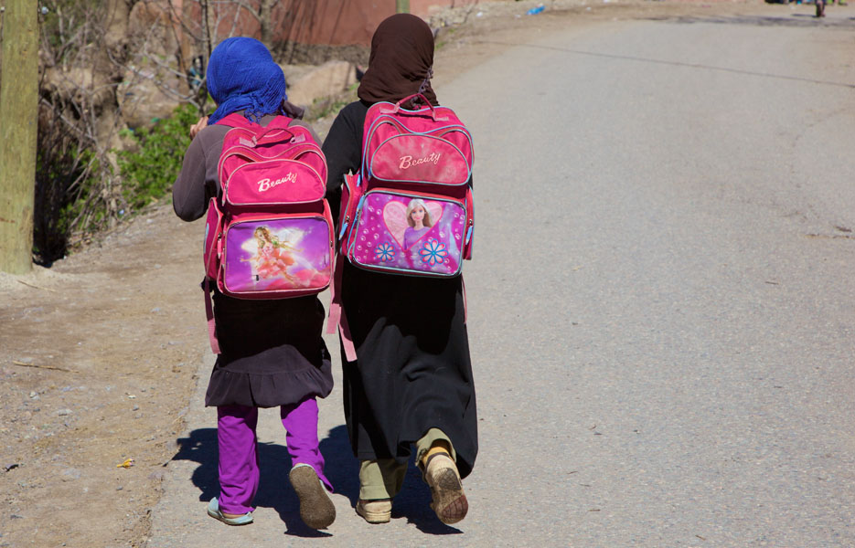 Two schoolgirls wearing headscarves and beauty schoolbags on their backs walk along a road in Imlil / Marrakech / Morocco