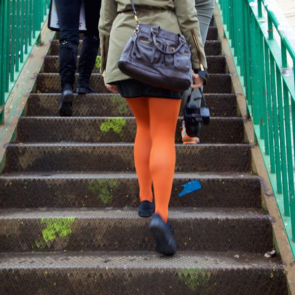 Beine in Orange gehen zwischen einem Geländer in Grün eine Treppe hinauf