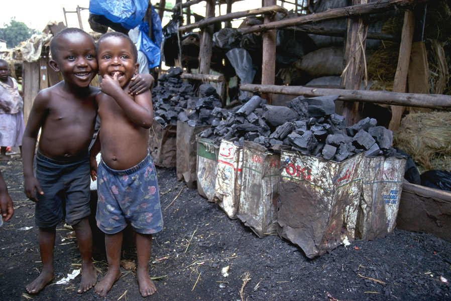 Two dark-skinned children are standing arm in arm on a charcoal market in Kampala / Uganda